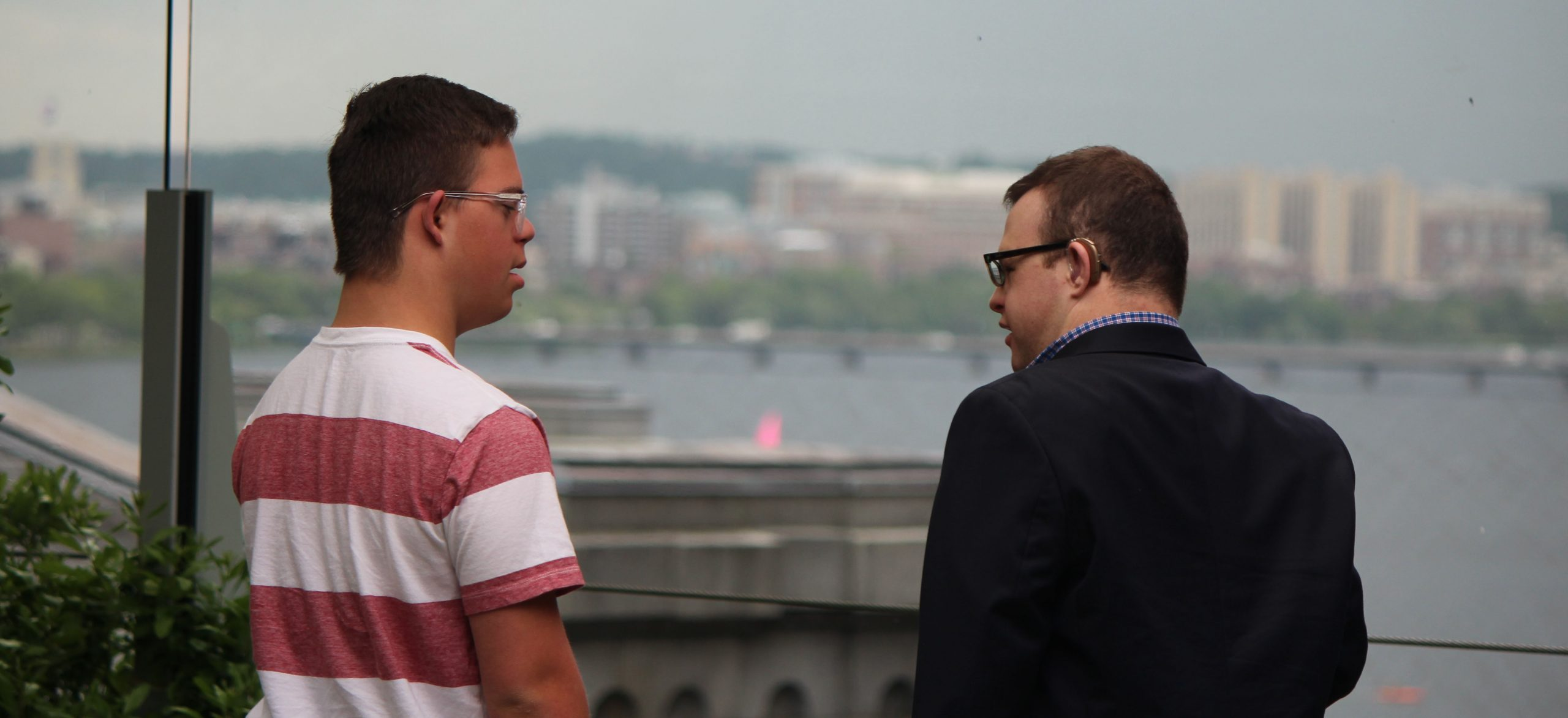 Two men stand with their backs to the camera. They are standing outside, in an area overlooking a river in the distance. They are turned to each other, as if they are speaking.