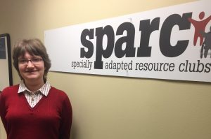 A woman wearing a red sweater and button up shirt stands against a wall. A sign occupies the wall with SPARC - specialty adapted resource club printed.