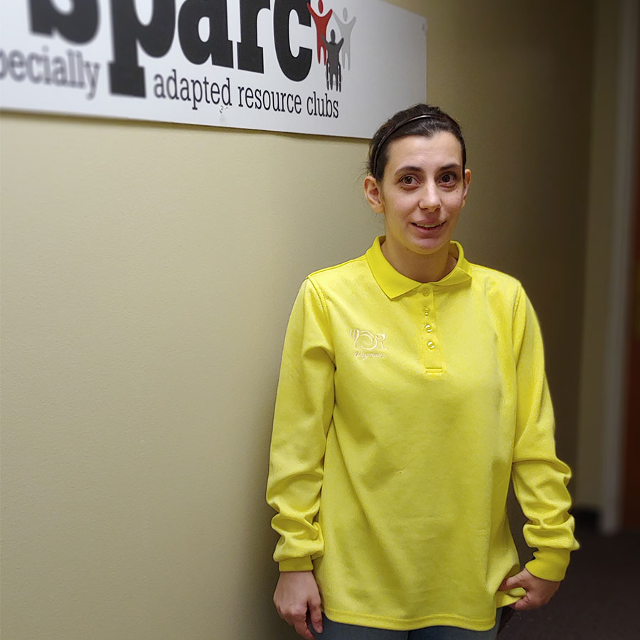 A person stands before a wall, wearing a yellow button up shirt.